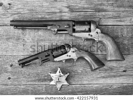 The guns that won the west and  sheriff badge in black and white. - stock photo