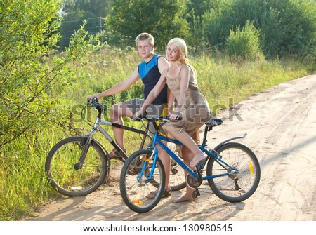 The guy and the girl by bicycles on the rural road in the summer evening
