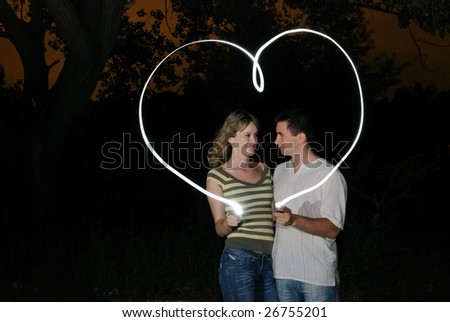 The guy and the girl draw heart a finger. Isolate on black - stock photo