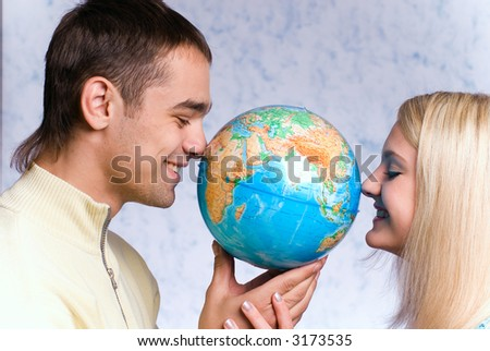 The guy and the girl hold the globe on a blue background - stock photo