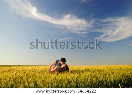 The guy and the girl kiss in a autumn field - stock photo