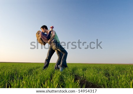 The guy and the girl kiss in a spring field