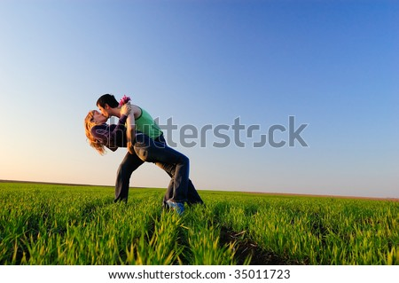 The guy and the girl kiss in a spring field - stock photo
