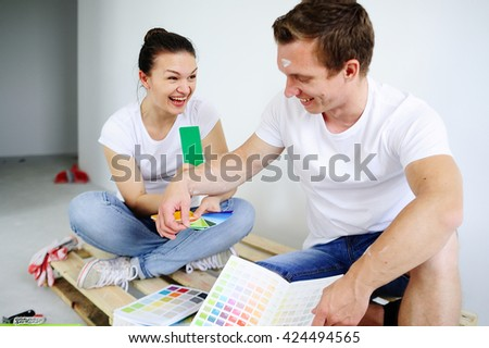 The guy and the girl to choose the color of paint for the repair. Young people sit on the wooden pallet. About them catalogs are spread out. Couple selects color of paint. Him it is very cheerful - stock photo