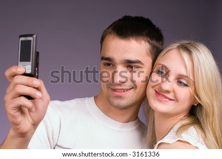 The guy and the girl with mobile phone on a grey background - stock photo
