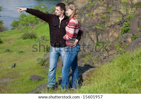 The guy embraces the girl against rocks and specifies in something - stock photo