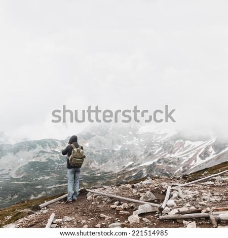 The guy from the back with a backpack in the mountains, take pictures