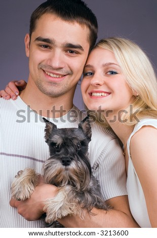 The guy, girl and dog smile on a grey background - stock photo
