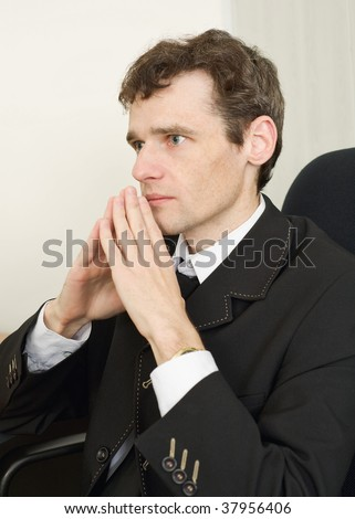 The guy in a black jacket sits having combined hands - stock photo