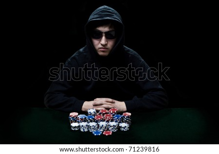 The guy in dark glasses, the player in gamblings sits at a table before it a heap poker chips - stock photo
