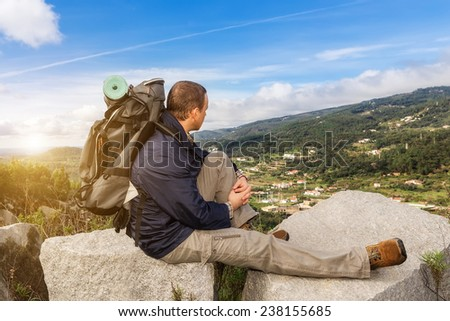 The guy in the campaign with a backpack, at sunset. In the mountains with stunning views. - stock photo