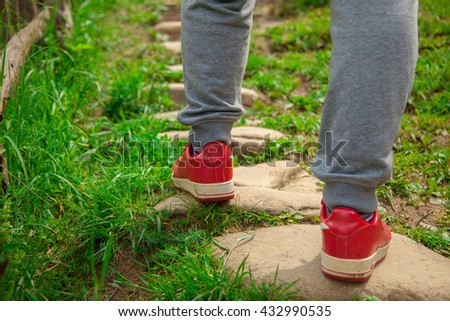 the guy in the red sneakers walking on the old stone path