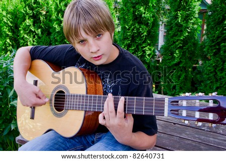 The guy is learning to play guitar - stock photo