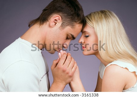 The guy kisses hands to the girl on a grey background