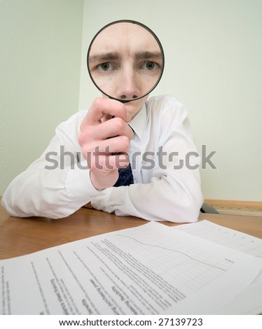 The guy looks through the big magnifier