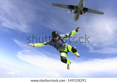 The guy parachutist jumps out of an airplane. - stock photo