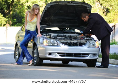 The guy repairs the car, the girl smiles - stock photo