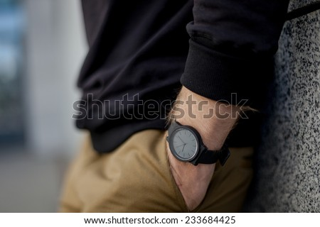 the guy standing near the wall on a city street. fragment of a hand with a wristwatch - stock photo