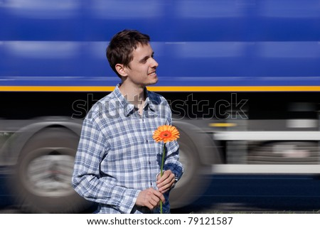 The guy with a flower in a hand waits the girl who promised to keep the appointment. He feels all emotions of love