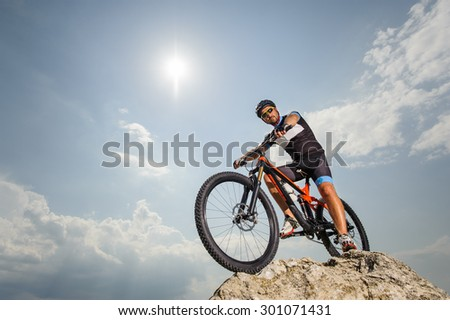 the guy with the bike on top of the mountain - stock photo