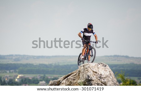 the guy with the bike on top of the mountain looking down - stock photo