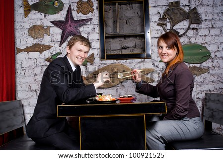 The guy with the girl eat sushi - stock photo