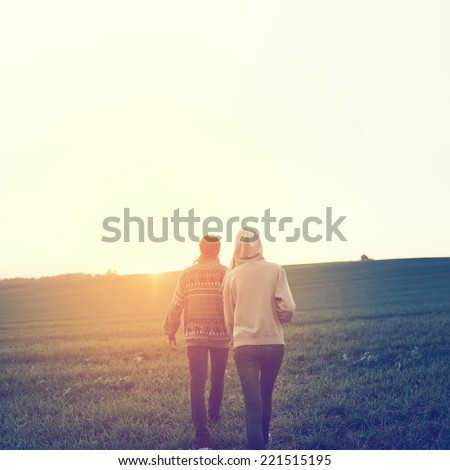 The guy with the girl from the back, go hand to sunset - stock photo