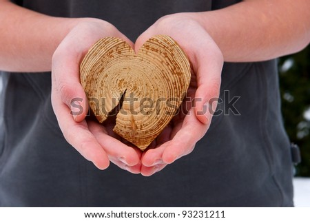 The guy with the wooden heart in his hands, giving it to somebody. - stock photo
