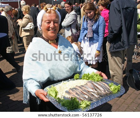 THE HAGUE, HOLLAND - JUNE 12: Fishing woman presents freshly caught herring on the annual Vlaggetjesdag festival (celebrating the first herring catch) June 12, 2010 in Scheveningen, Holland - stock photo