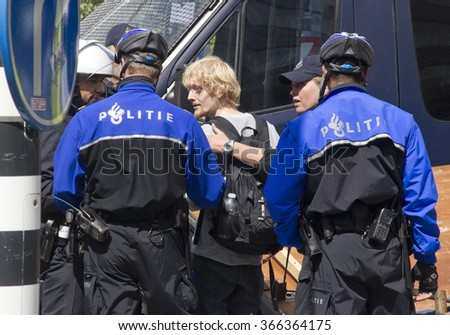 THE HAGUE, HOLLAND - JUNE 18, 2011: Police arrest demonstator during anti-fascist demonstration against fascist demonstration in The Hague, Holland on June 18, 2011 - stock photo