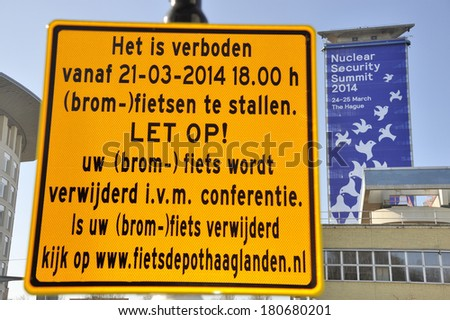 THE HAGUE, HOLLAND-MARCH 9: Large banner on a building announcing the Nuclear Security Summit 2014 in The Hague. Traffic sign in Dutch no bike parking  March 9, 2014 The Hague, Holland  - stock photo