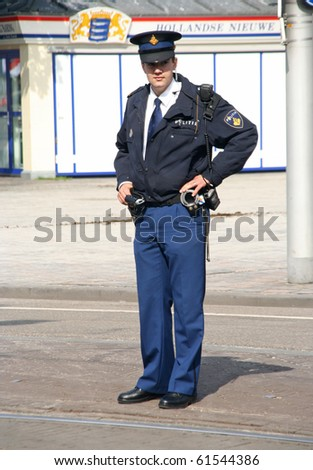 THE HAGUE, HOLLAND - SEPT 21: Young police officer watching the crowd at the Parliament on Prinsjesdag (opening of parliamentary year by Queen) on September 21, 2010 in The Hague, Holland. - stock photo