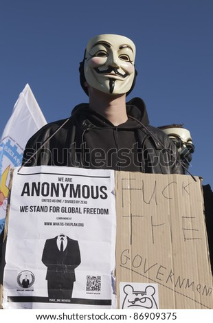 THE HAGUE – OCTOBER 15: An unidentified masked member of Anonymous holding anti government banner during the Occupy protest on October 15, 2011 in The Hague, The Netherlands. - stock photo