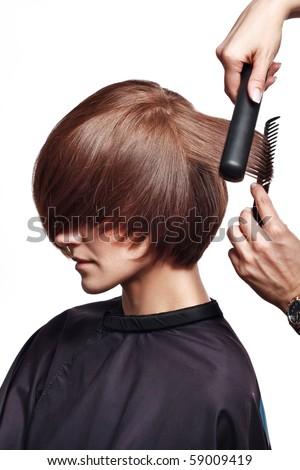 The hairdresser brushes the girl - stock photo