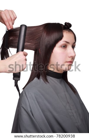 The hairdresser brushes the girl
