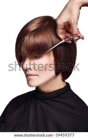 The hairdresser cuts the hair - stock photo