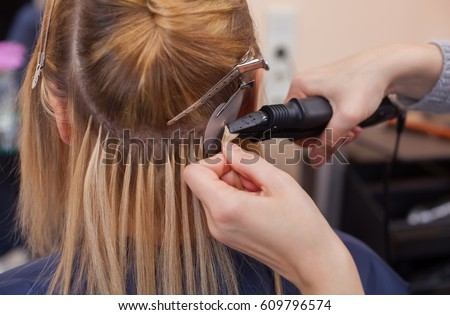 Hairdresser does hair extensions young girl stock photo 609796574 the hairdresser does hair extensions to a young girl a blonde in a beauty salon pmusecretfo Image collections