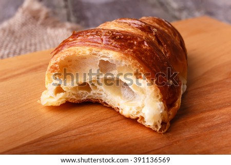 The half of fresh baked different croissant on wooden table in rustic style