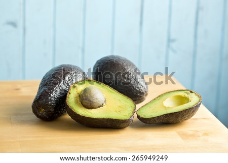 the halved avocado on kitchen table - stock photo