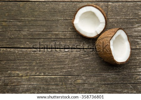 the halved coconut on old wooden background - stock photo