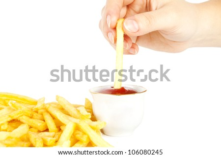 The hand dips a potato in ketchup - stock photo