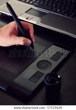 The hand draws a pen on a working surface of a tablet - stock photo