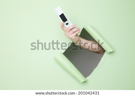 The hand holding a mobile phone - stock photo