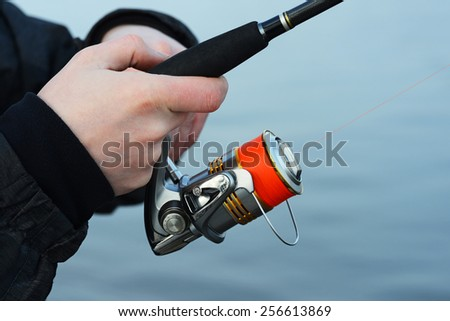 the hand holding the fishing rod