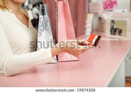 The hand holds a credit card against a counter - stock photo