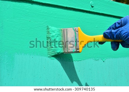 the hand holds the brush to paint - stock photo