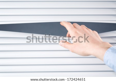 The hand of a business woman opening closed shutters or blinds.