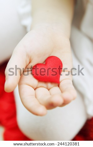 The hand of a little girl holding a small heart