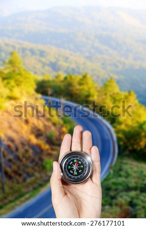 The hand of a man holding a magnetic compass over a landscape road view - stock photo