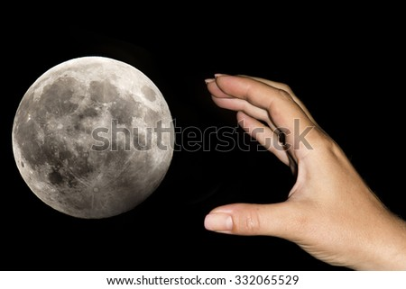 The hand of a woman is taking the moon over a black sky. Conceptual image for aspirations, daydreams, will impossibilities, have exaggerated claims, never being content with what you have - stock photo